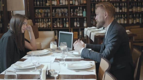 Cover Image for Young Beautiful Woman and Mature Man with Beard Having Business Dinner with Laptop Computer in