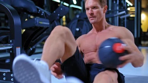 Young Male Athlete Shakes the Press in the Gym, Does Exercises with a Ball. Professional Athlete