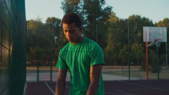 Basketball Player Dribbling Ball Outdoor at Dawn
