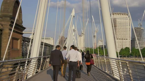 Thumbnail for Business people and tourists walking on a bridge