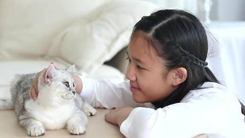 Nettes asiatisches Kind spielt mit schottischem Kätzchen zusammen