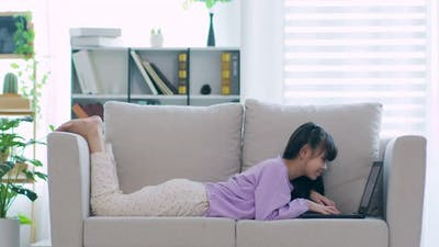 cute girl children using computer laptop on sofa online learning and meeting online
