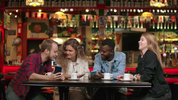 Thumbnail for A Multiethnic Group of Students, Three Europeans and an African American, Look at the Phone Screens