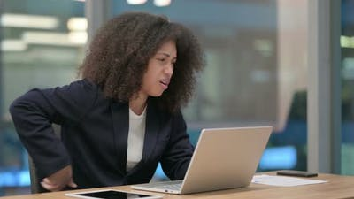 African Businesswoman with Laptop Having Back Pain