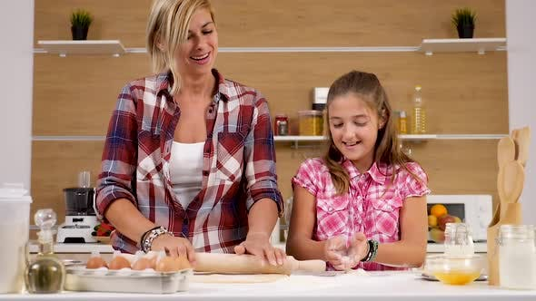Thumbnail for Young Daughter Throws Flour in the Air While Her Mother Knead Dough Next To Her