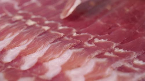 Traditional spanish food jamon. Macro. A fork pierces a cured meat delicacy