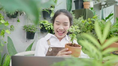 Front view of Happy Asian young woman selling plants online