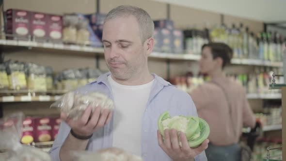 Uncertain Man Choosing Unhealthy Gingerbread Cookies or Healthy Cabbage in Grocery. Portrait of