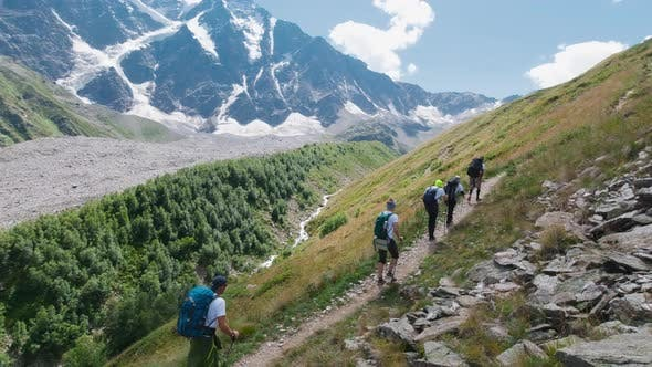Active tourists go to mountains on a sunny day