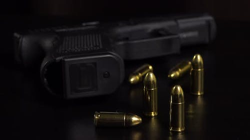 Closeup on Bullets and a Gun on a Black Table