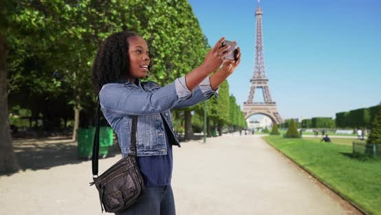 Thumbnail for Black female recording her adventures in Paris, Eiffel Tower in background