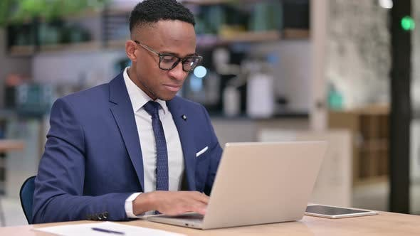Thumbnail for African Businessman with Laptop Pointing at the Camera