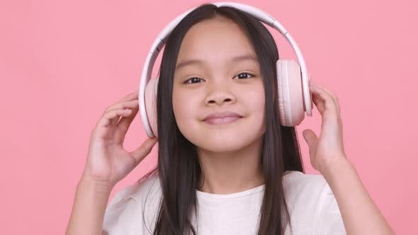Cute Little Asian Girl in Wireless Headphones Listening to Dynamic Music Dancing and Smiling to