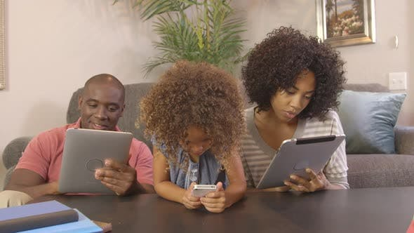 Thumbnail for African American family in the living room playing on phones and tablets
