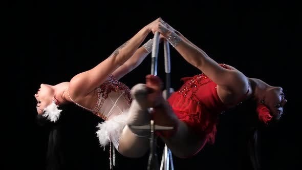 Thumbnail for Two Woman in Makes Graceful Element in the Aerial Hoop. Black Background. Slow Motion. Close Up
