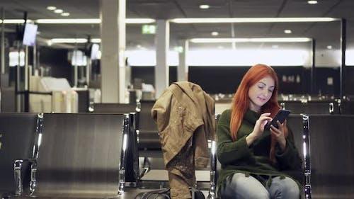 Junge Frau verwendet Telefon in Flughafenterminal