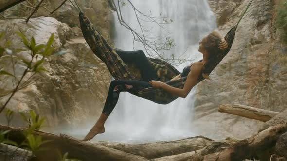 Thumbnail for Girl Relaxes in Hammock at Close Bright Waterfall