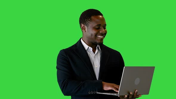 Thumbnail for Handsome African American Businessman Standing and Working on Laptop on a Green Screen, Chroma Key