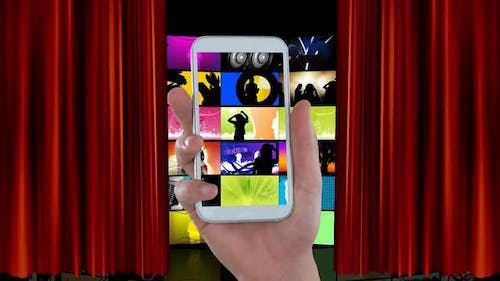 Hand holding a mobile phone and videos on LCDs