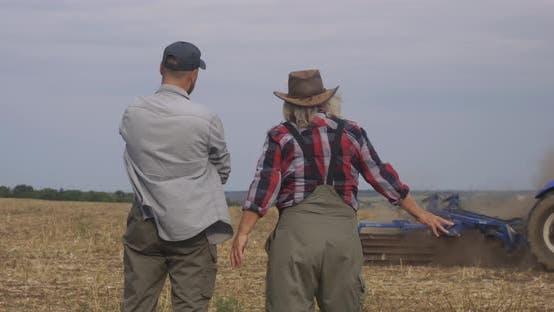 Glad Elderly Farmer Showing Soil Fertility To Successor
