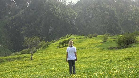 Thumbnail for Blond Haired Alone Woman is Watching View in Yellow Flowery Meadow to Forest