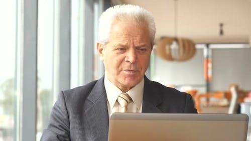 Senior Businessman Drinks Hot Beverage at the Cafe