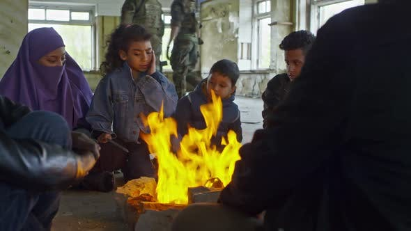 Thumbnail for Refugees Relaxing by Fire in Abandoned Building