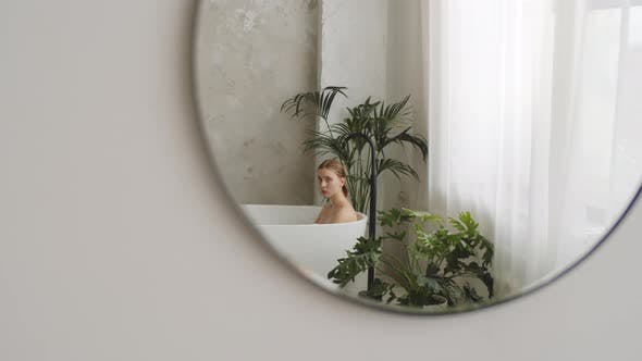 Thumbnail for Woman Sitting in Bathtub and Looking in Mirror