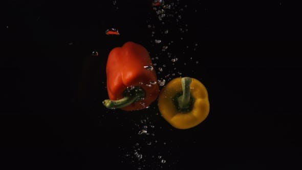Thumbnail for Yellow and Red Peppers with Water Droplets Collide on Black Background, Vegetables Falling Into