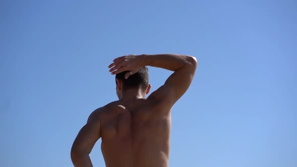 Thumbnail for Muscular Shirtless Man Stretching Arms Against Blue Sky