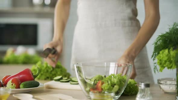 Cover Image for Cooker Cutting Fresh Cucumber Into Slices and Adding It Into Bowl with Salad