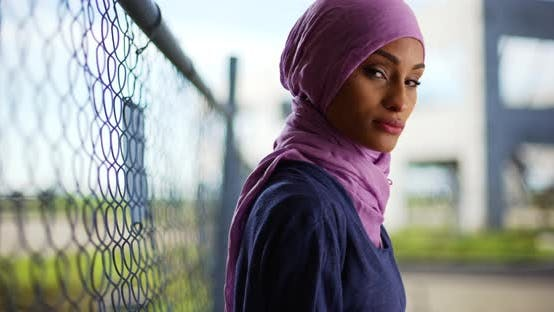 Thumbnail for Black woman in hijab standing by chain-link fence, looking at camera confidently