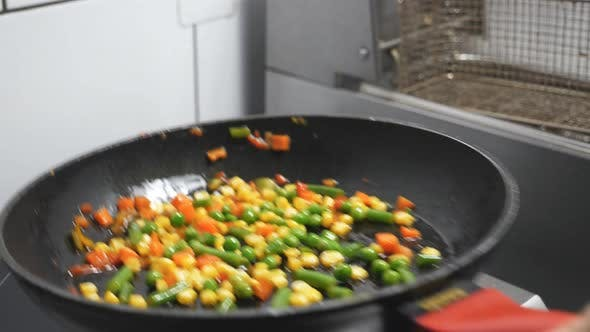 Male Arm of Cook Holding Skillet and Tossing Up Mixed Vegetables at Kitchen Restaurant