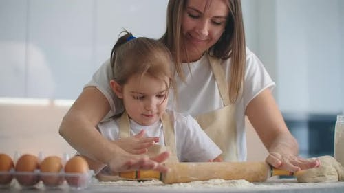 Daughter and Mother at Home in the Kitchen in Aprons Pour Flour Roll Out with a Rolling Pin and