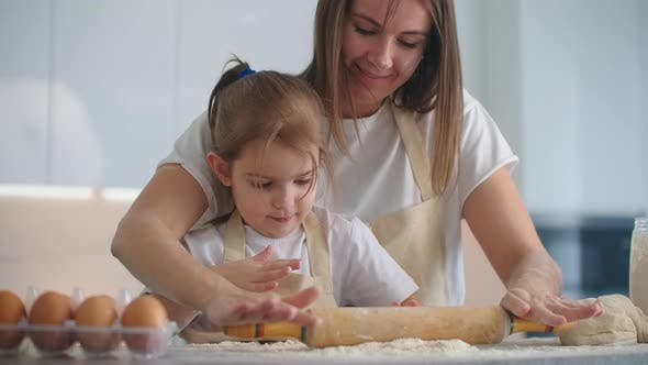 Thumbnail for Daughter and Mother at Home in the Kitchen in Aprons Pour Flour Roll Out with a Rolling Pin and