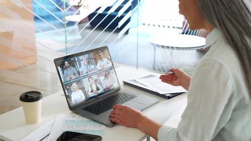 Asian Older Businesswoman Having Working Video Chat in Contemporary Office
