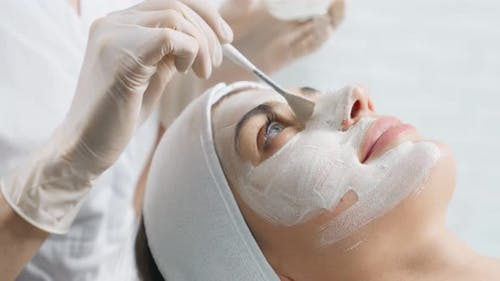 Young Woman on Cleaning Face in Professional Beautician