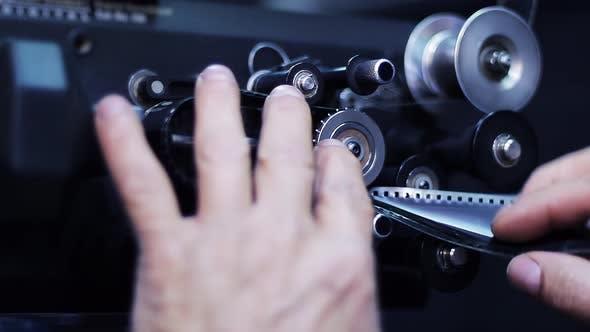 Man Hands putting Filmstrip into Vintage Film Projector. 4K Version.