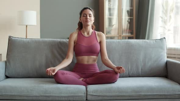 Woman Sitting in Padmasana on Couch
