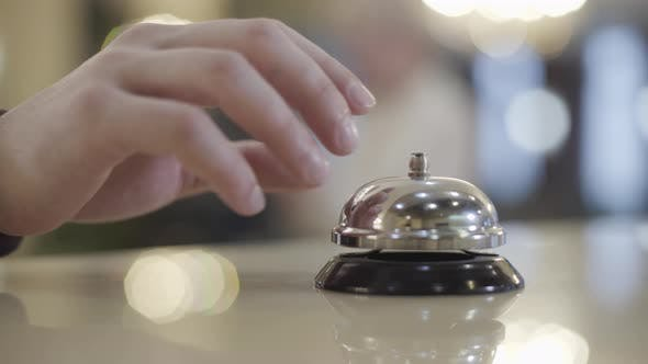 Extreme Close-up of Unknown Caucasian Man Pressing Hotel Bell