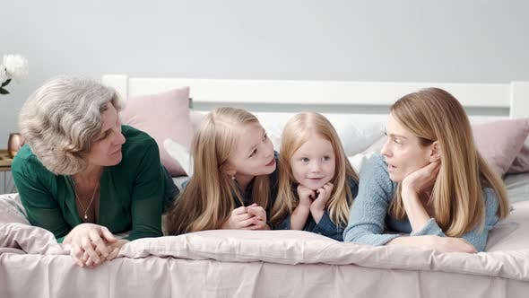 Three Generations of Women Laying on the Bed