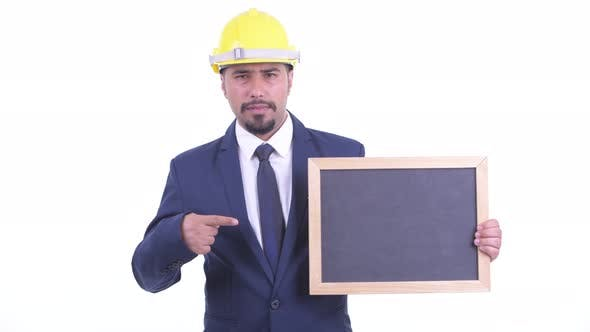 Thumbnail for Stressed Bearded Persian Businessman As Engineer Holding Blackboard and Giving Thumbs Down