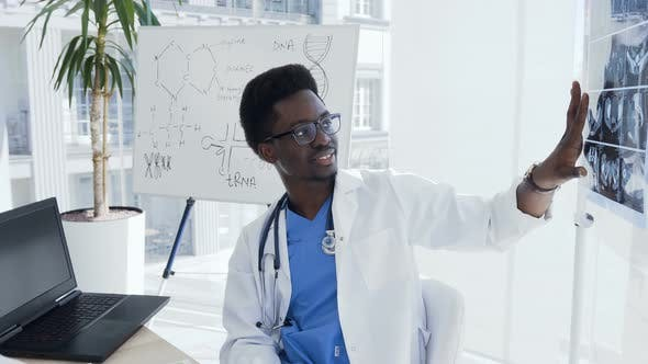 Young Afro American Doctor with X-ray of Female Lungs and Pelvis is Meeting