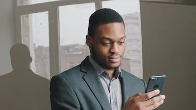 African American Guy Look at Cell Phone Screen