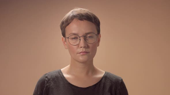 Thumbnail for Caucasian Woman with Short Haircut Wears Glasses in Studio on Beige Background