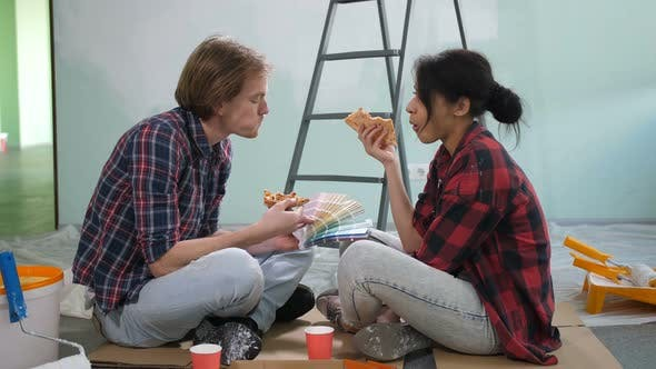 Thumbnail for Couple Choosing Color From Palette, Eating Pizza
