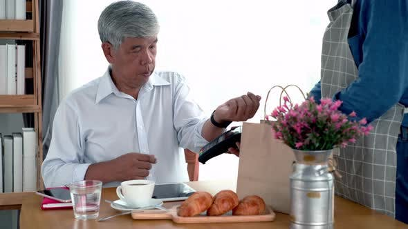 Thumbnail for Elderly Asian Man Using a Smart Watch Mobile Payment 12