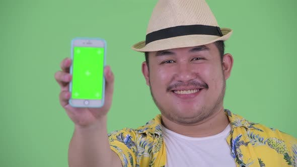 Cover Image for Face of Happy Young Overweight Asian Tourist Man Showing Phone