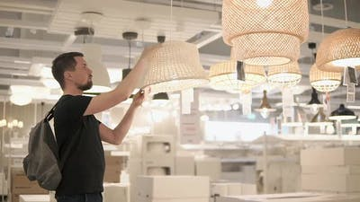 An Adult Male Who is in a Shopping Boutique is Considering Floor Lamps for Lamps