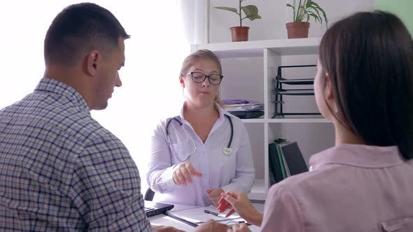 Young Couple at Doctor Appointment in a Fertility Clinic, Female Gynecologist Tells About the of